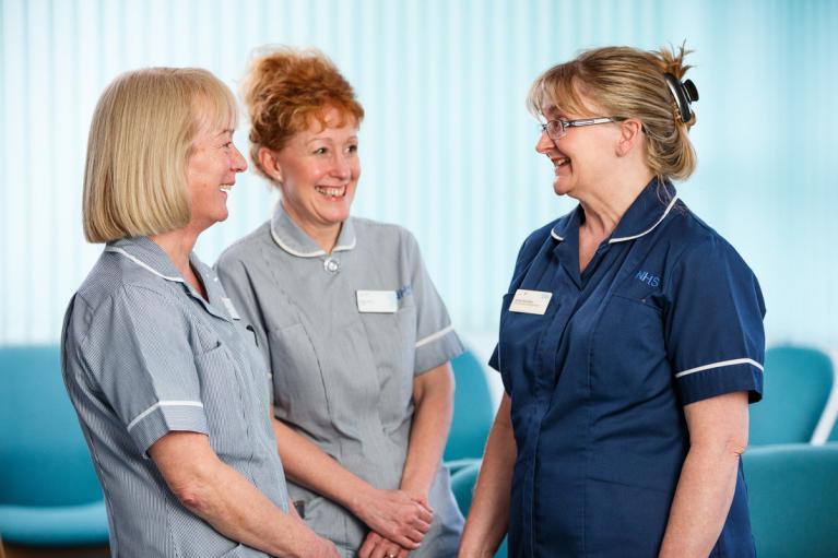 three female nurses smiling and talking